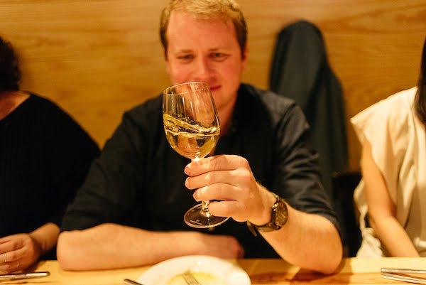 Luke girando una copa de vino blanco