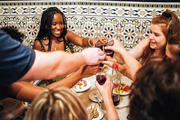 Grupo de personas brindando con vino tinto en un bar de tapas