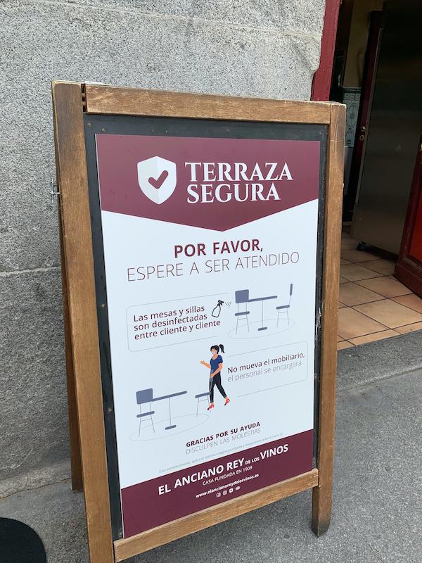 Protocolos de seguridad y salud COVID-19 listados en una terraza en España