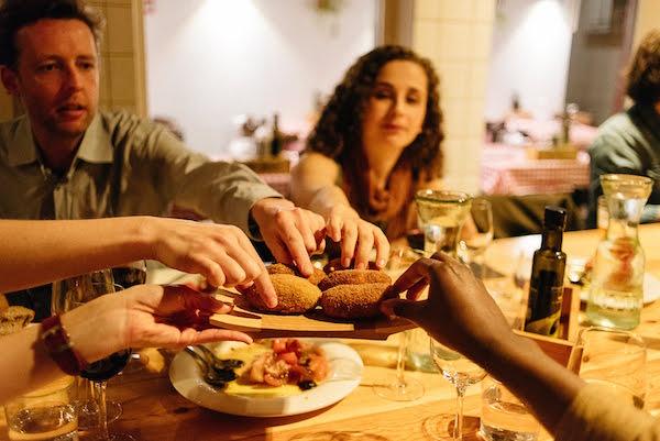 Personas pasando un plato de comida alrededor de una mesa.