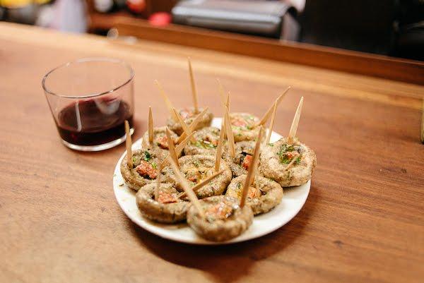"""Setas a la plancha rellenas de chorizo, ajo y perejil con una copa de vino tinto junto con """"srcset ="""" https://madridfoodtour.com/wp-content/uploads/mush-meson-del-champiñón-madridrooms .jpg 600w, https://madridfoodtour.com/wp-content/uploads/mushrooms-meson-del-champiñón-madrid-300x201.jpg 300w, https://madridfoodtour.com/wp-content/uploads/mushrooms-meson -del-champiñón -madrid-330x220.jpg 330w """"tamaños ="""" (ancho máximo: 600px) 100vw, 600px"""