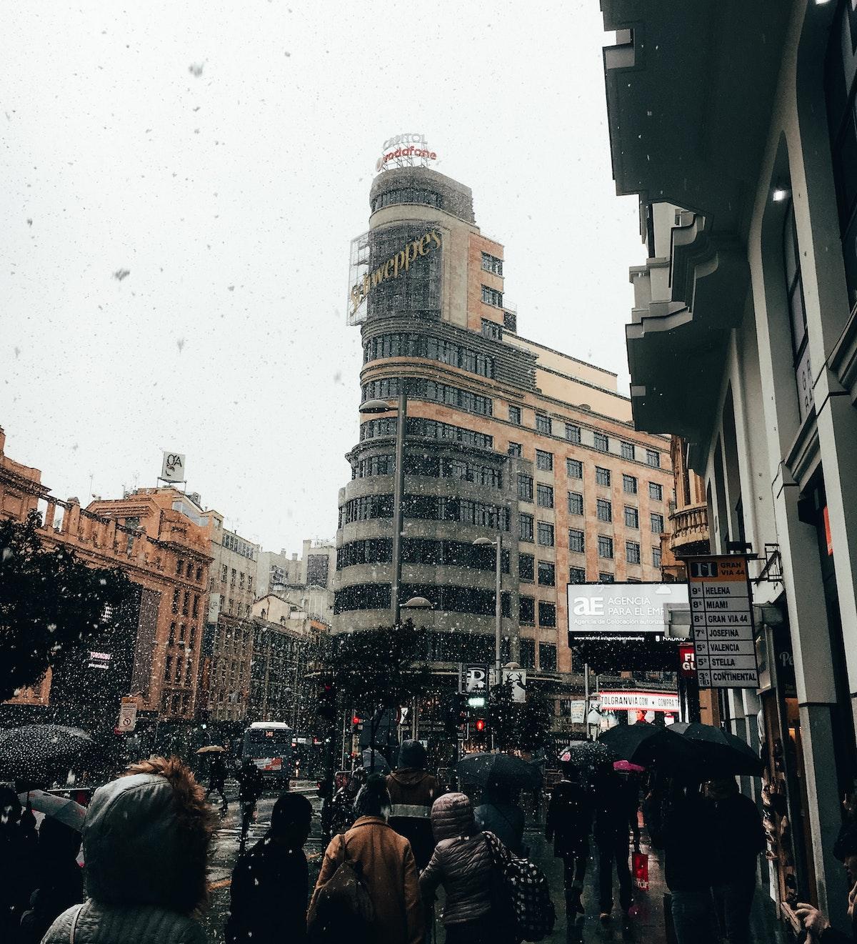 Gente caminando con sombrillas en una concurrida calle de la ciudad en un día lluvioso en Madrid.
