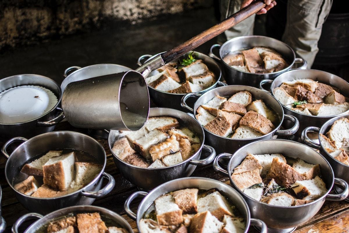 Varios frascos de sopa de ajo con trozos de pan hirviendo a fuego lento en una estufa