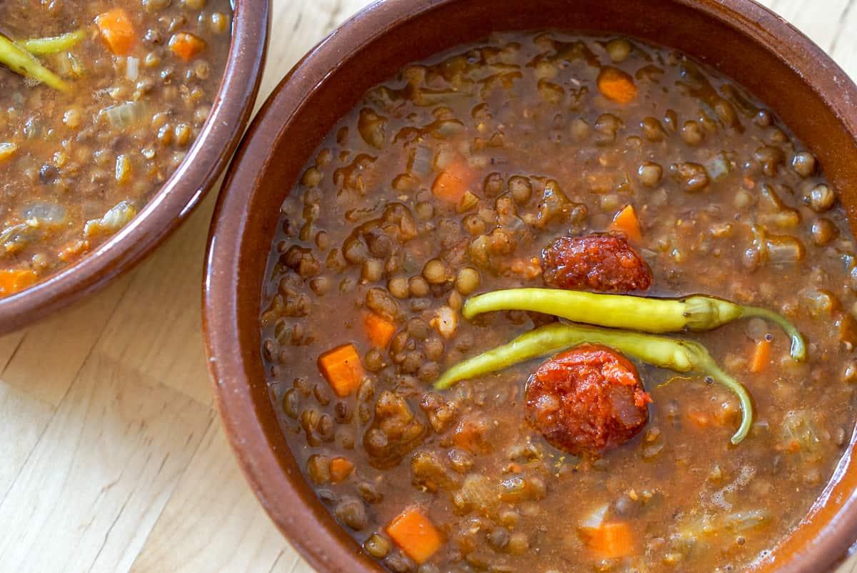 Tazón de sopa de lentejas con chorizo y pimientos verdes encurtidos
