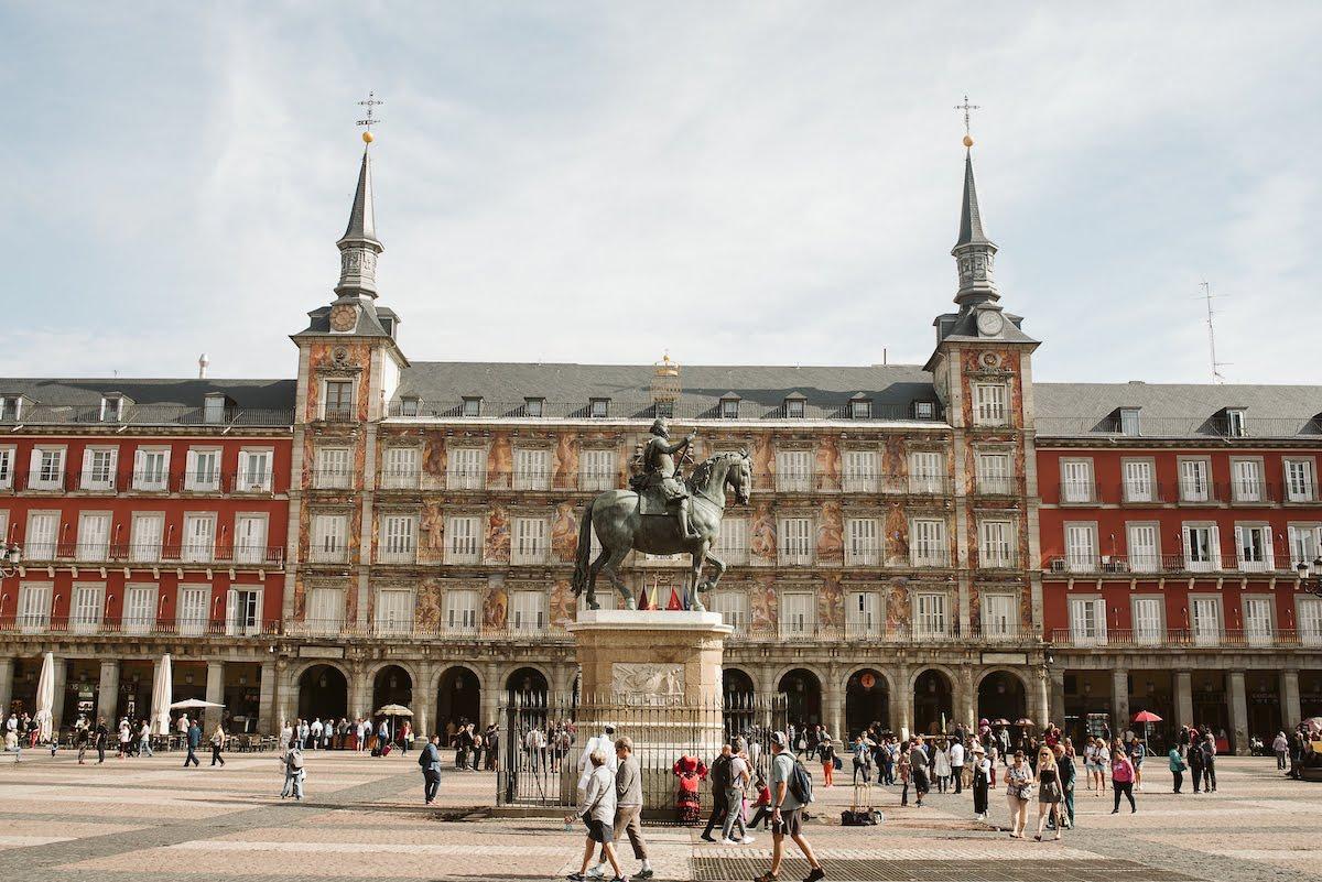 Vista del edificio central de la Plaza Mayor de Madrid con una estatua de un hombre a caballo en primer plano.