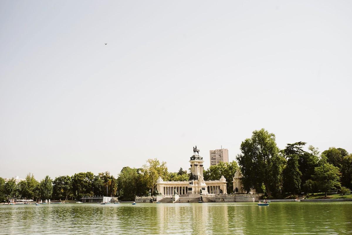 Pequeños botes de remos en el lago del Parque del Retiro de Madrid con un monumento visible al fondo.
