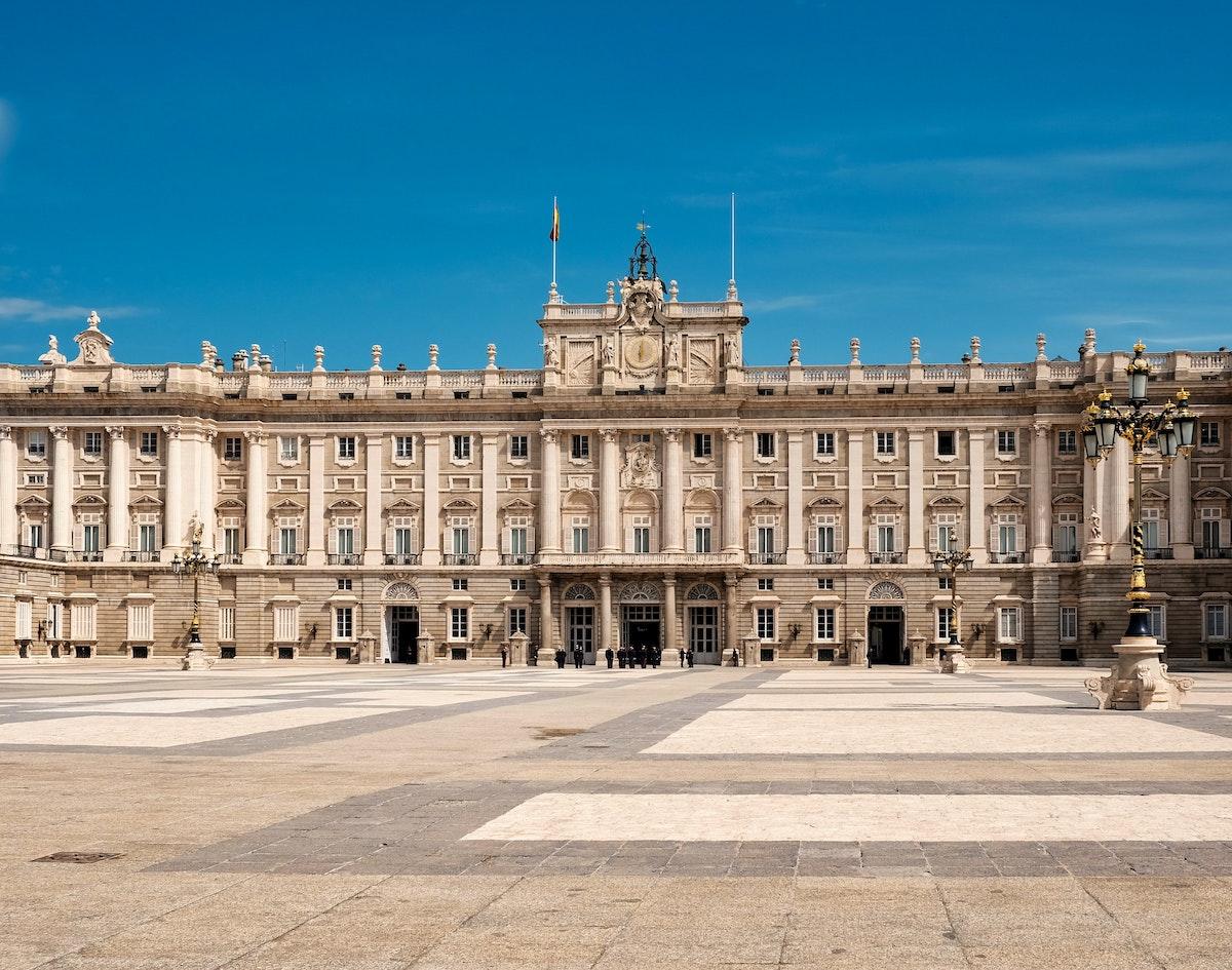 Exterior de un gran palacio real visto desde el otro lado de una vasta plaza en un día claro.