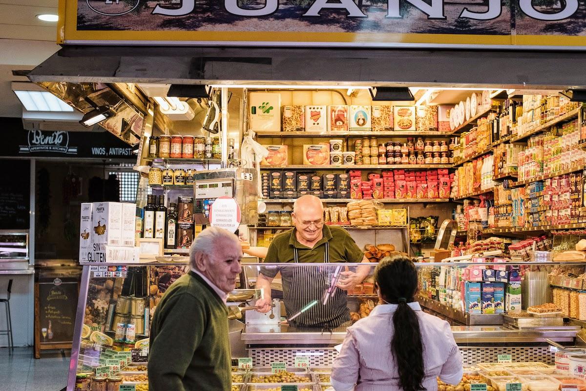 Vendedor en un puesto del mercado sonriendo mientras atiende a los clientes.