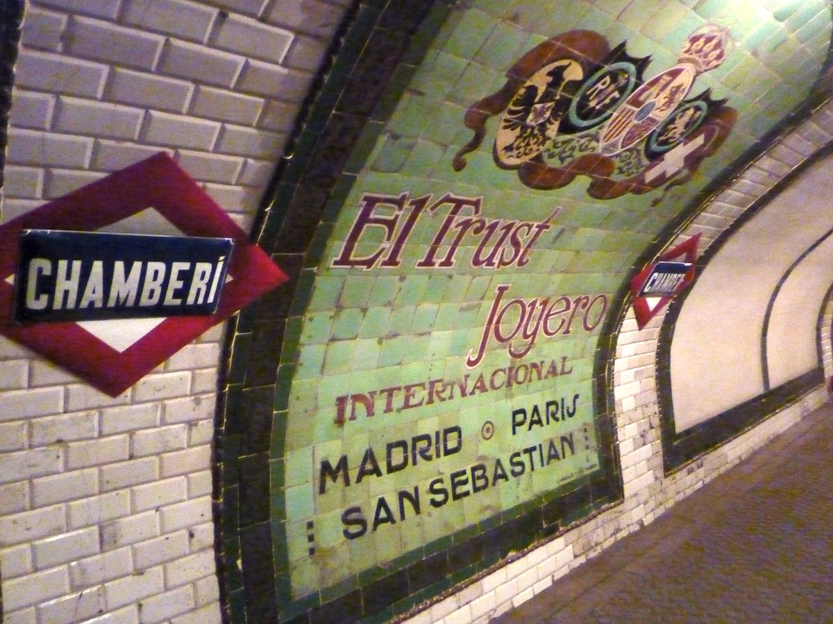 Anuncio vintage colorido con un fondo verde colocado en los azulejos de una antigua estación de metro.