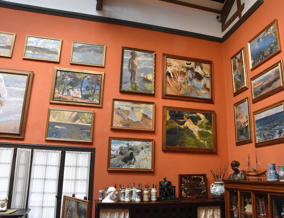 Habitación con paredes naranjas cubiertas de cuadros.