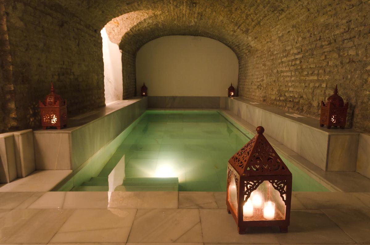 Interior de casa de baño de estilo árabe con paredes de ladrillo y una piscina rectangular. Un gran lugar para ir en Madrid cuando llueve.