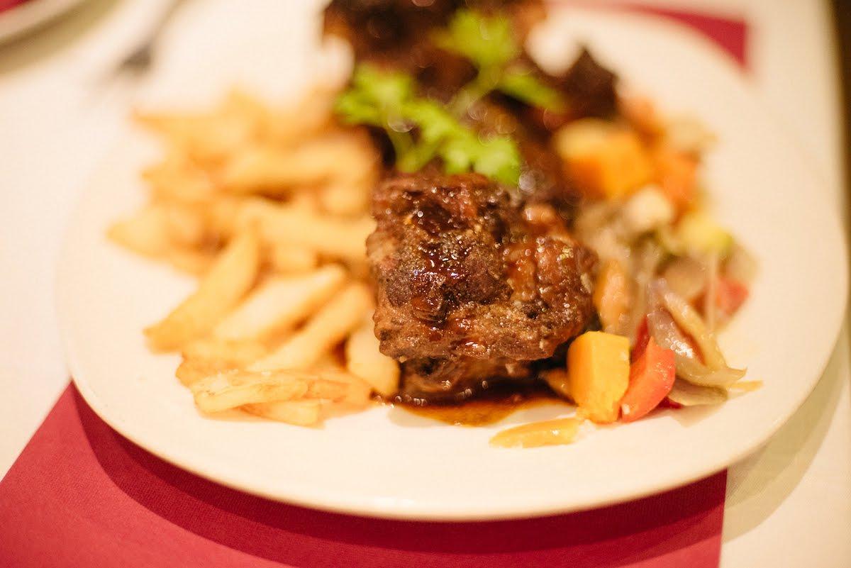 Plato de carne, patatas fritas y verduras salteadas