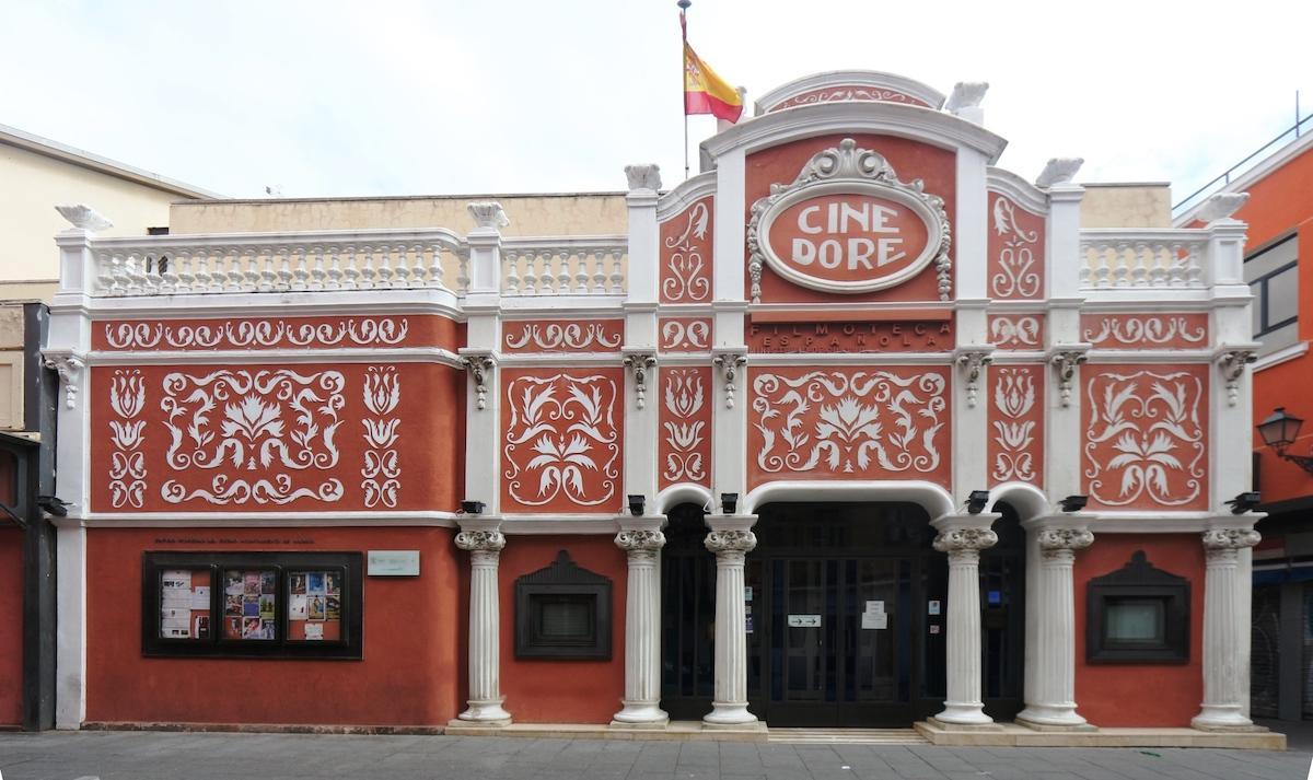 Exterior de una sala de cine histórica con piedra roja y columnas y detalles blancos.