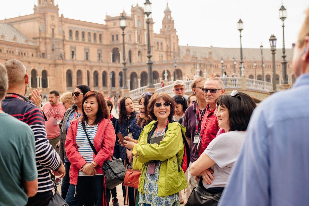 Un grupo de turistas conversando y riendo en una gran plaza rodeada de edificios de piedra marrón.