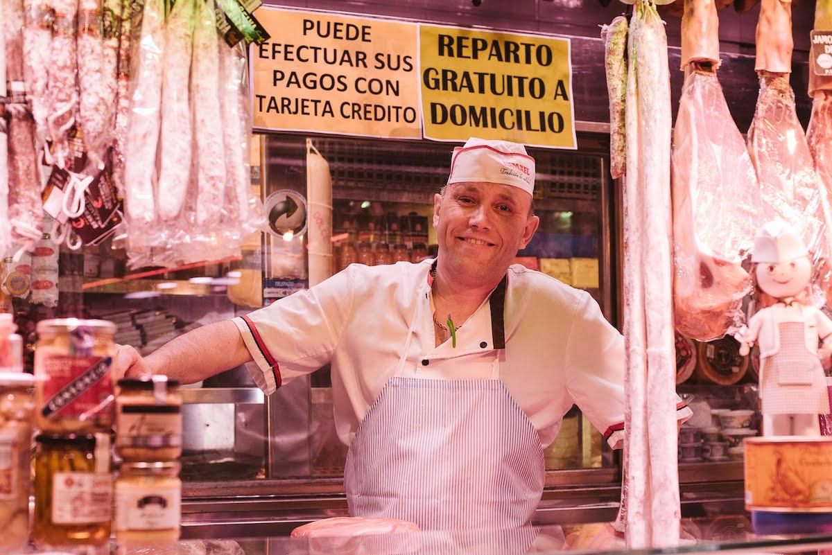 Un hombre sonriendo a un puesto de jamón y embutidos en un mercado de alimentos.