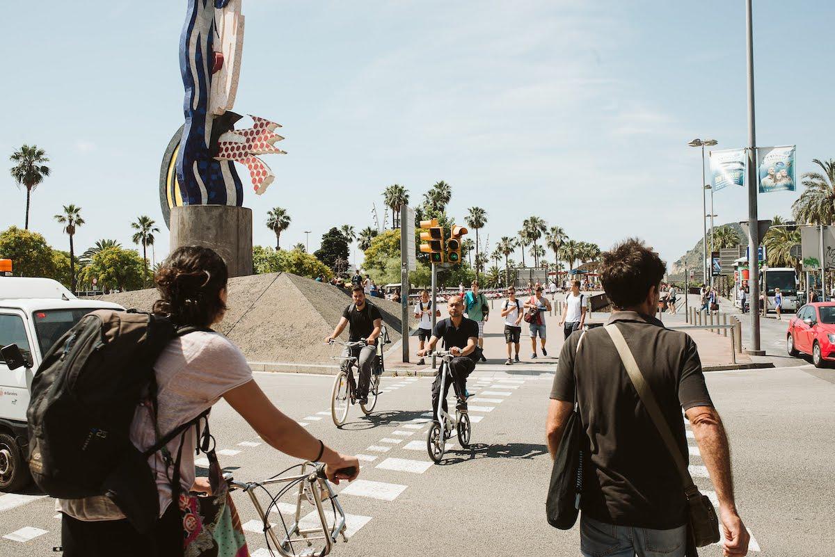 Peatones y ciclistas cruzando la calle en una intersección urbana.