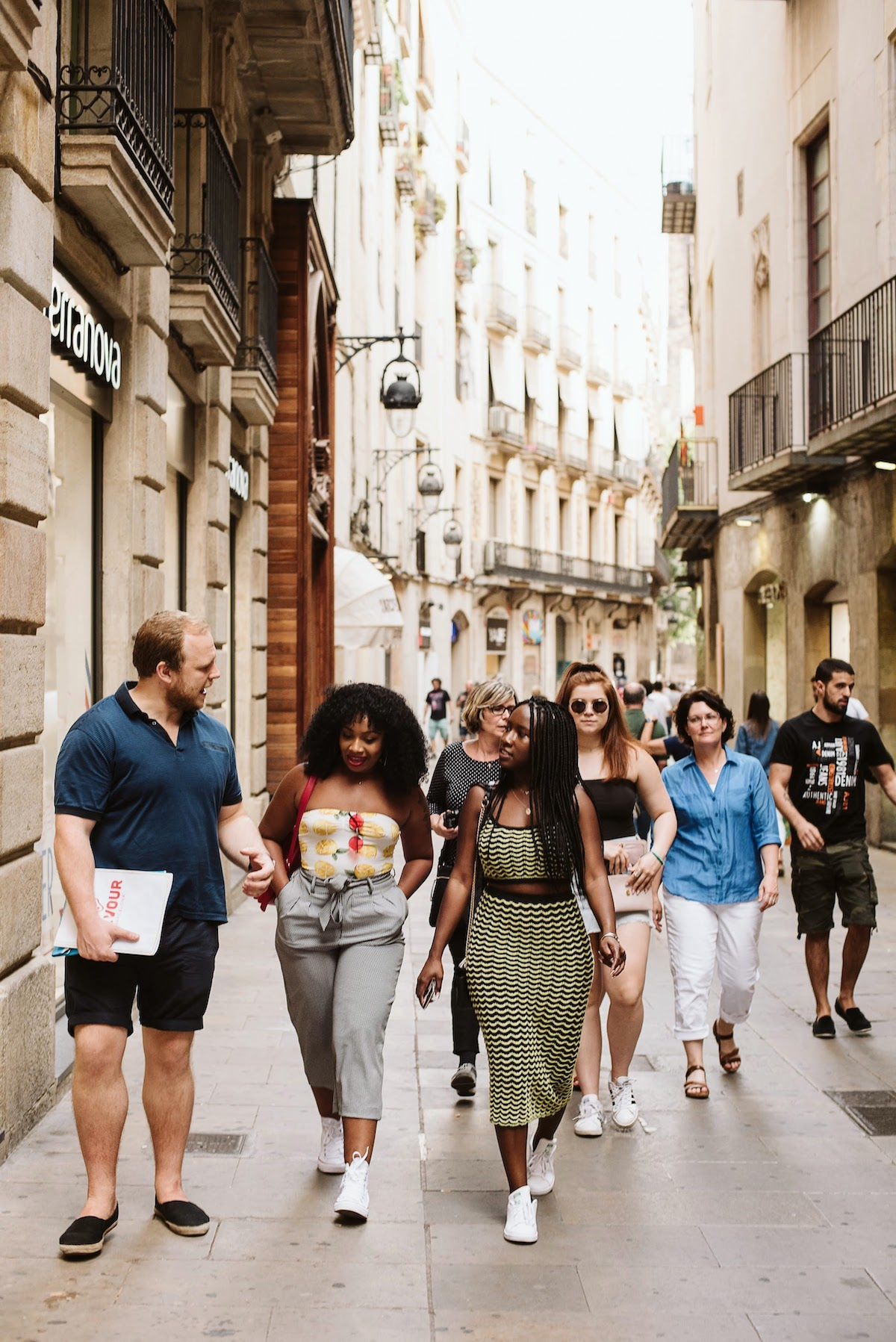 Pequeño grupo de turistas guiados por un guía caminando por una ciudad concurrida.