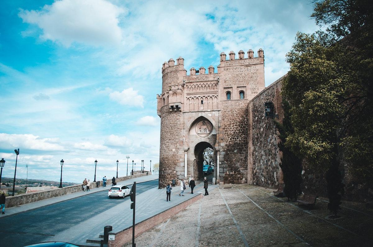 Gran torre histórica de piedra junto a una calle de la ciudad.