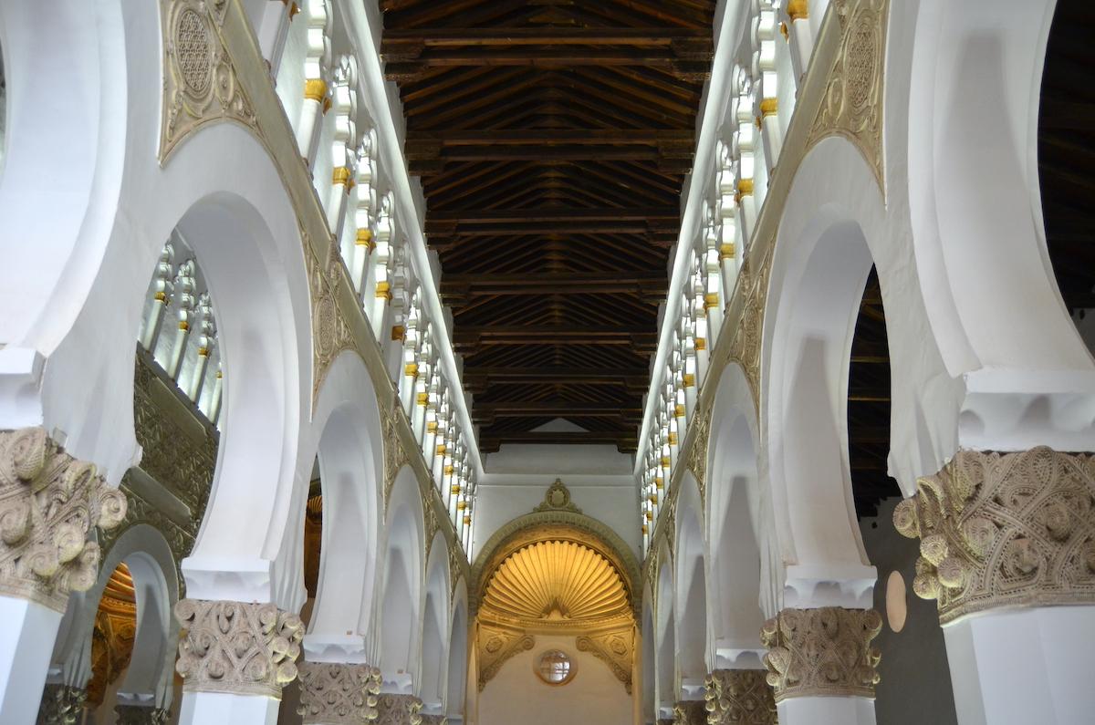 Interior de una sinagoga decorada con arcos blancos.
