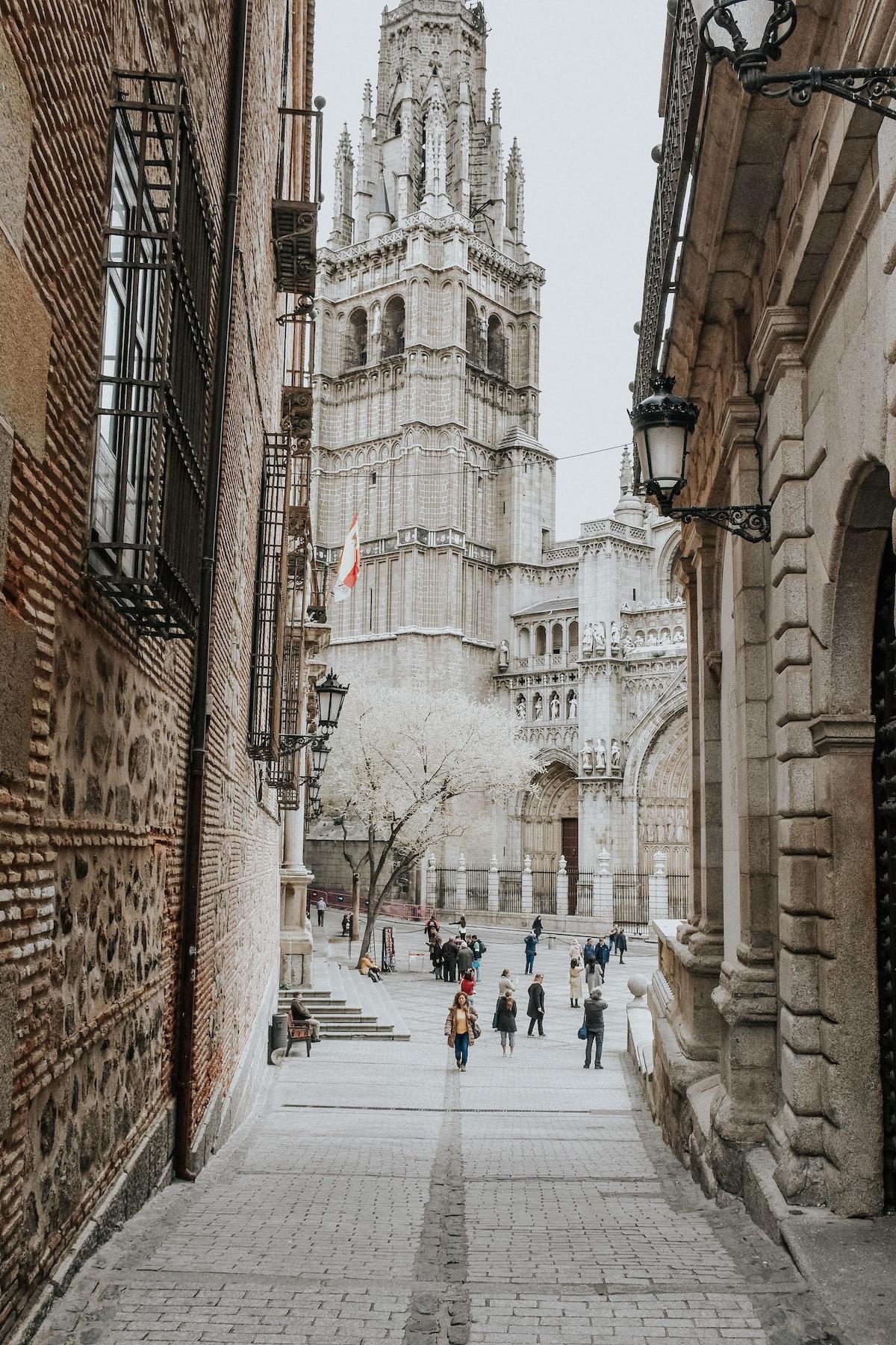 Calle frente a una gran catedral de piedra.
