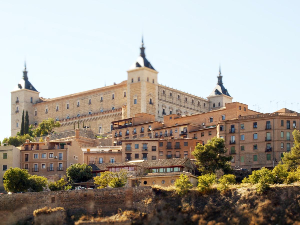 Gran fortaleza de piedra en una colina que domina una ciudad.
