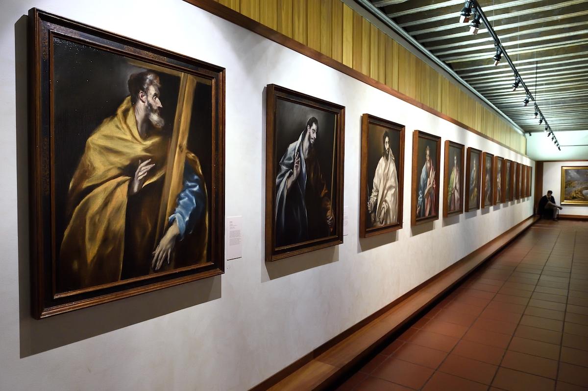 Conjunto de retratos de figuras religiosas colgadas en una pared blanca.
