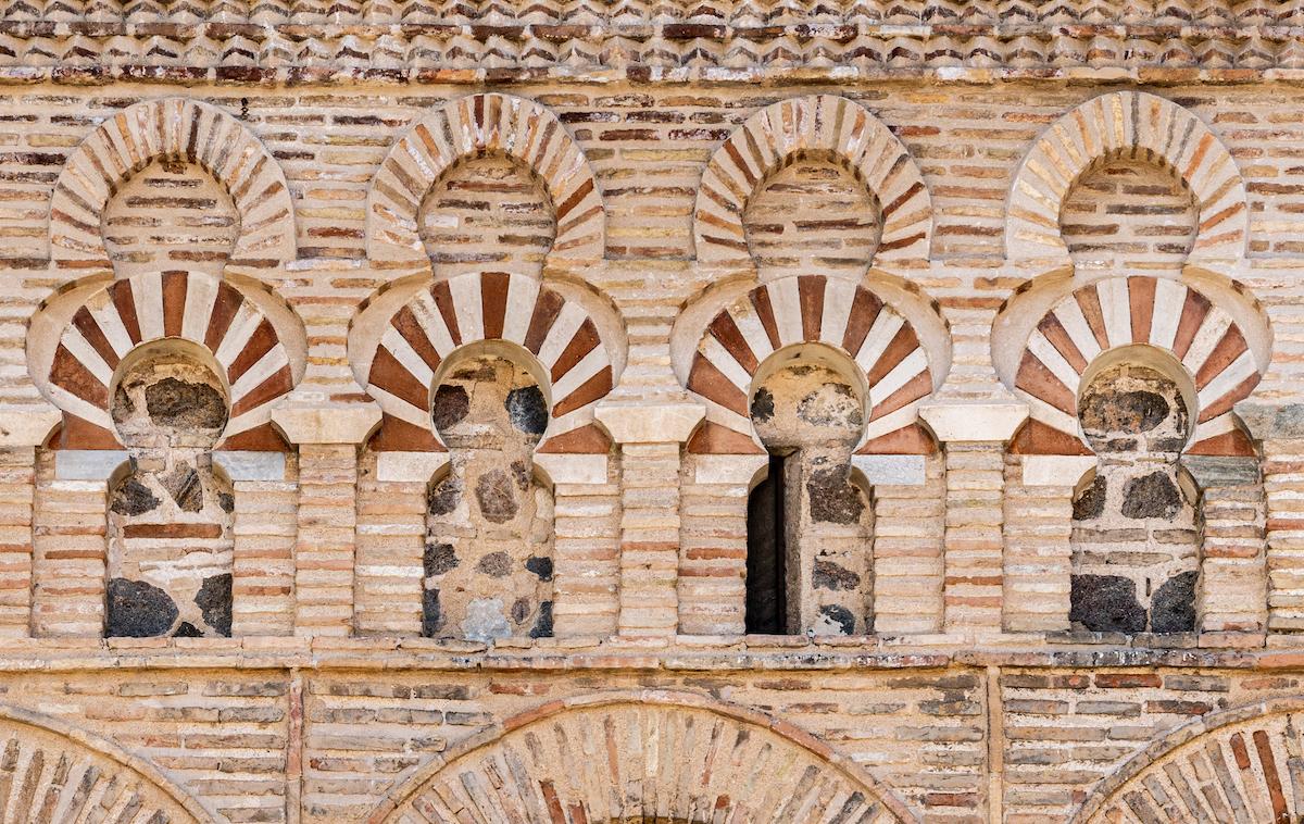 Vista cercana de pequeños arcos de ladrillo en la fachada de una mezquita.