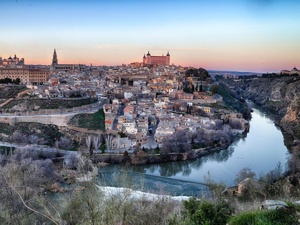 Vista panorámica de Toledo, España al atardecer tomada desde el otro lado de un río.