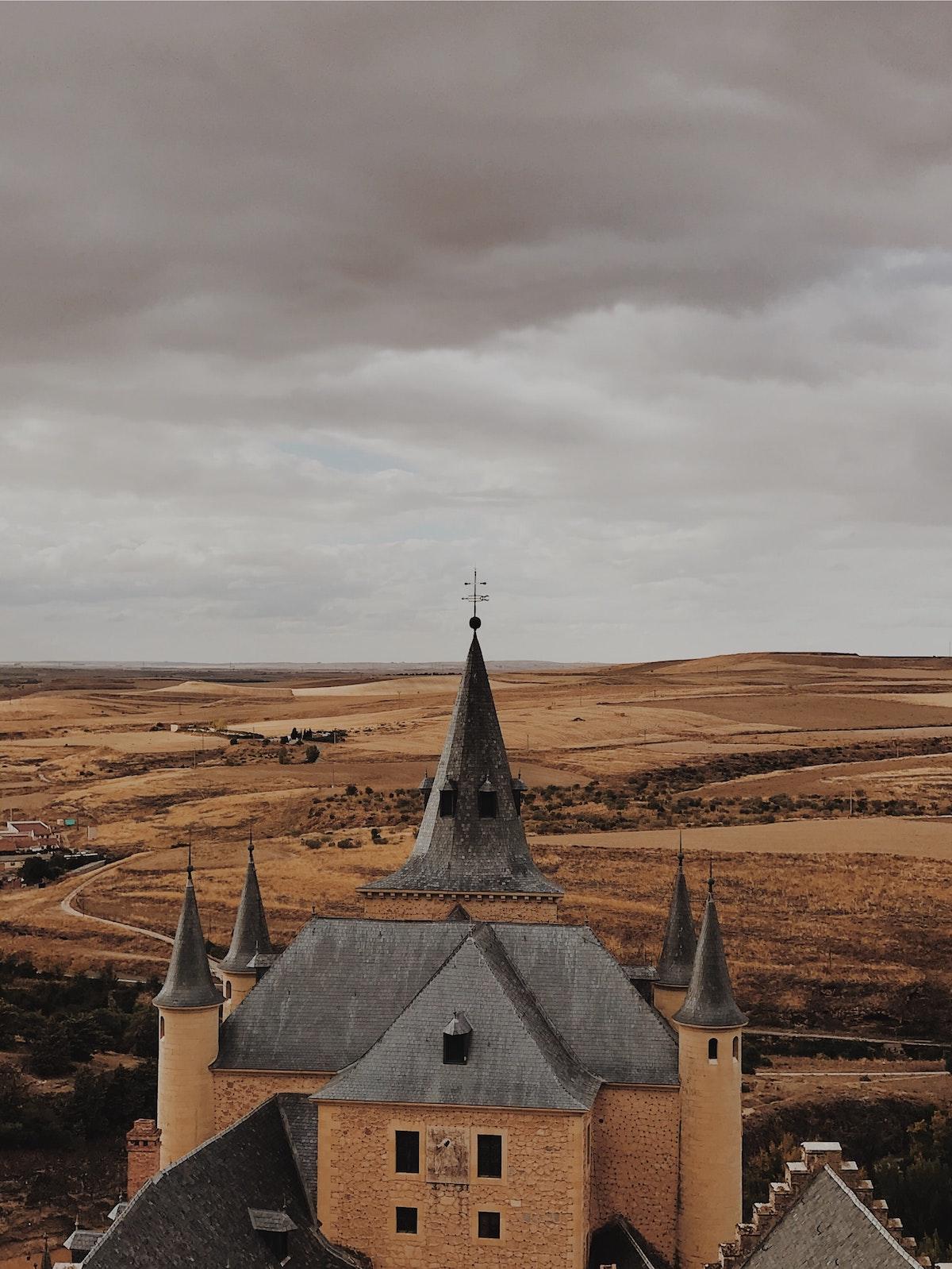 Vista del castillo medieval con torrecillas puntiagudas en tiempo nublado.
