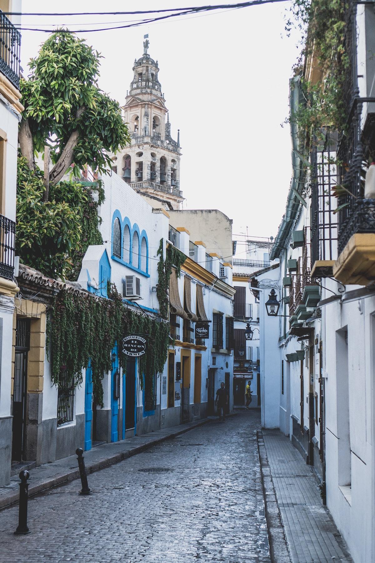 Calle adoquinada entre edificios blancos con una torre de catedral al fondo.