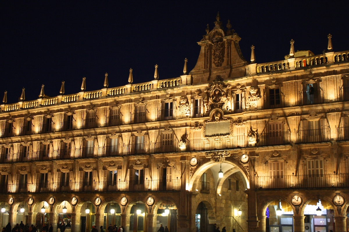 Fachada de un edificio histórico bien iluminado por la noche.
