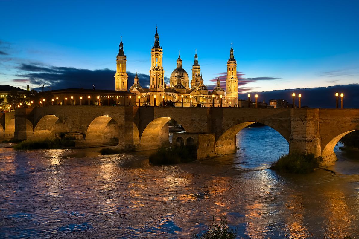 Vista de noche de la gran catedral y el puente arqueado de piedra.