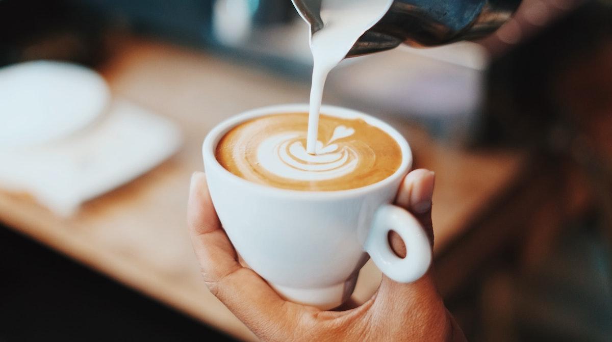 Cerca de barista vertiendo leche en una taza de café