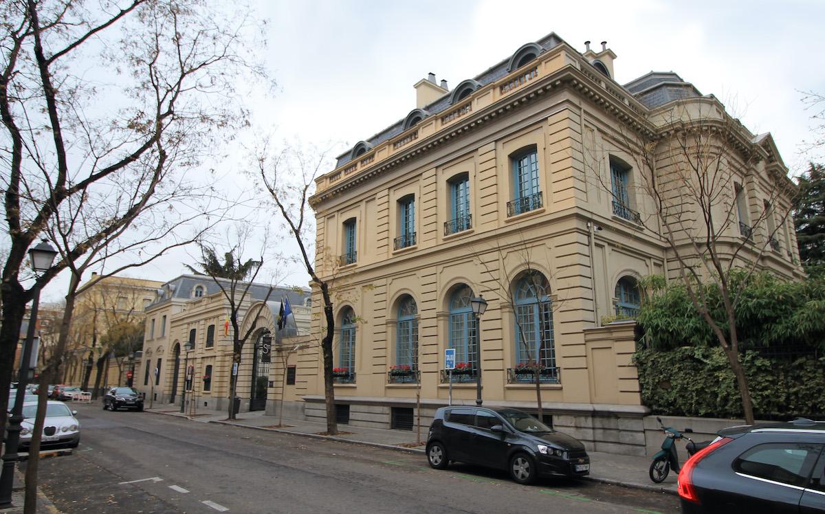 Fachada de un edificio de piedra beige de dos pisos en una calle de la ciudad.
