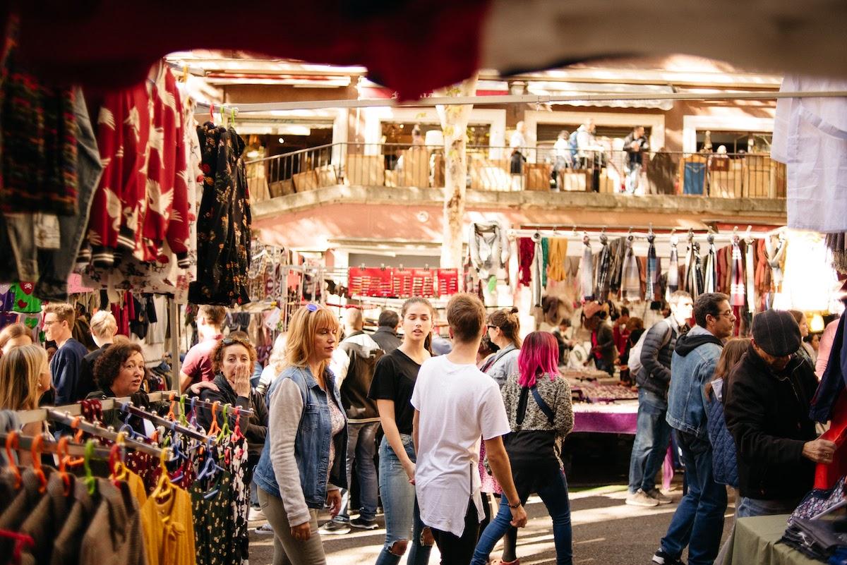 Multitud de personas caminando cerca de puestos de ropa en un mercado de pulgas.