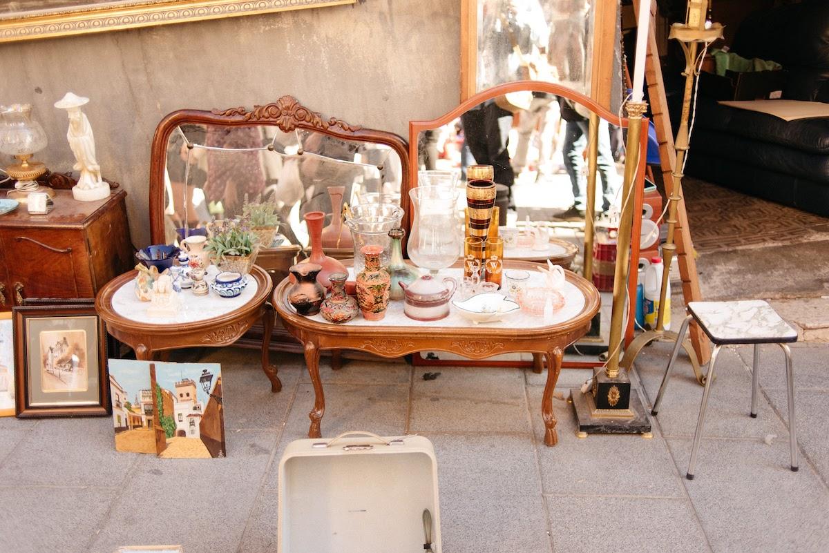 Antigüedades restauradas, incluidos muebles de madera y espejos a la venta en un mercado de pulgas.