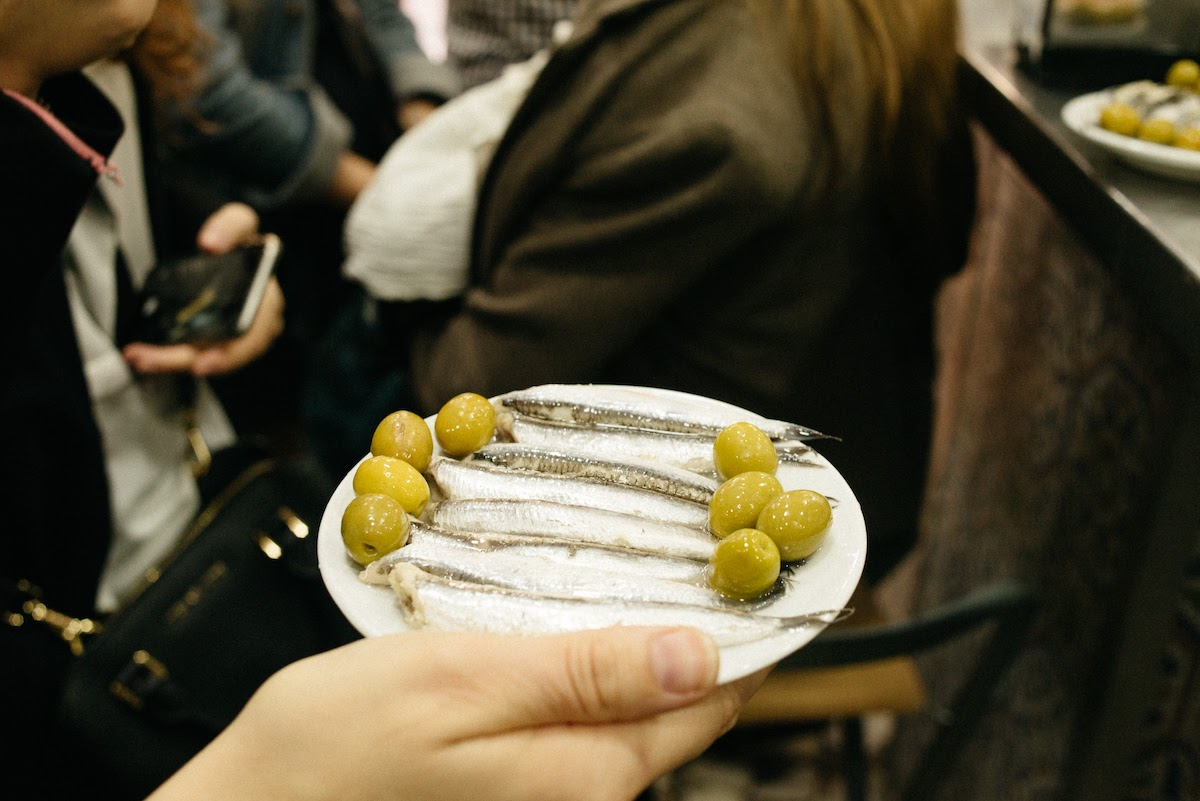 Mano de la persona sosteniendo un plato de anchoas y aceitunas verdes.