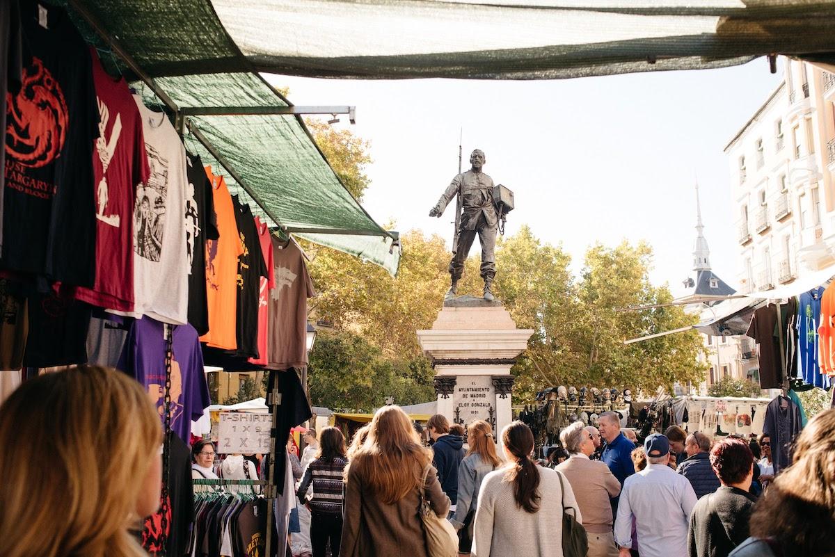 Los puestos del mercado de pulgas se instalan en una concurrida plaza que rodea una gran estatua de metal de un soldado.