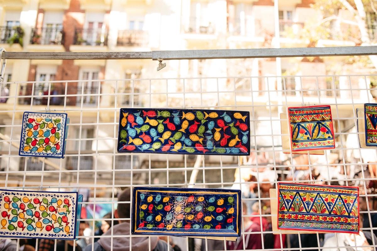 Bandejas de cerámica pintadas a mano de colores brillantes en exhibición en un mercado de pulgas.