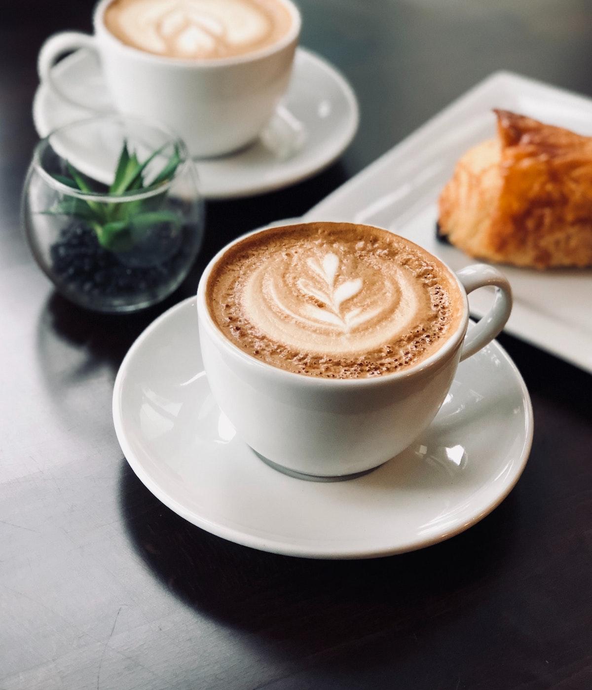 Dos cafés con leche en tazas blancas sobre una mesa junto a una pequeña planta en maceta y un pastel en un plato blanco.