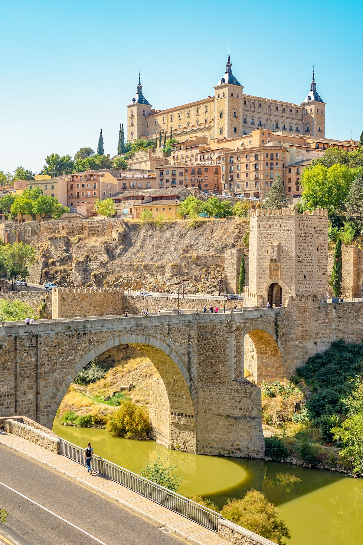 Puente de hormigón marrón sobre un río con edificios medievales al fondo.