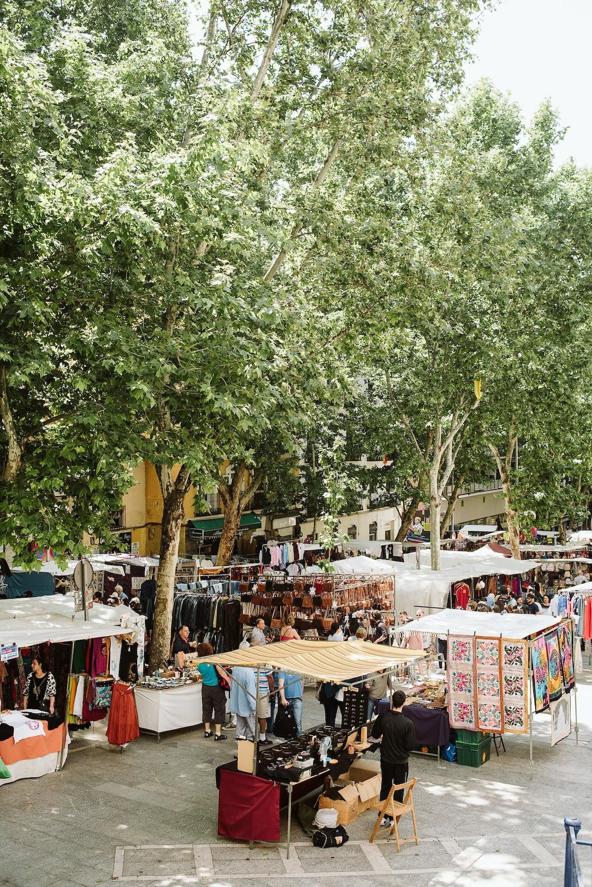 Puestos de mercado de pulgas bajo frondosos árboles verdes.