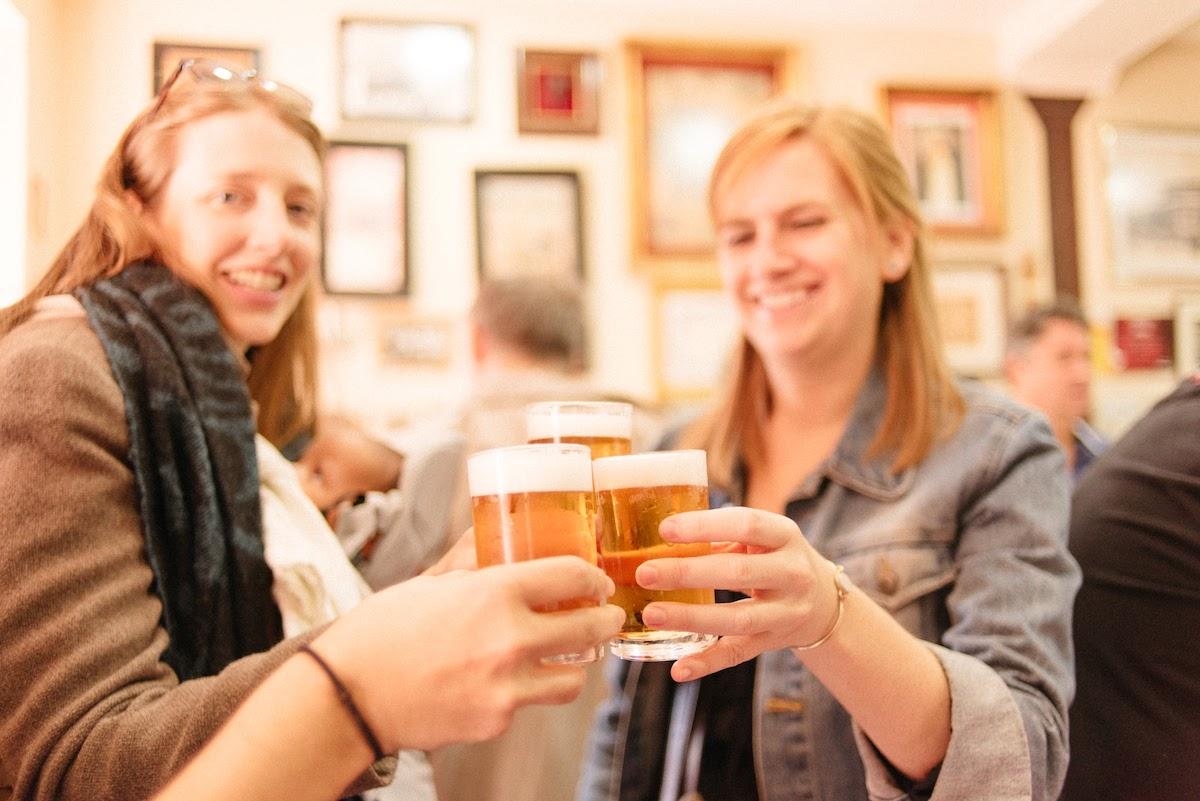 Un grupo de mujeres brindando con pequeños vasos de cerveza.