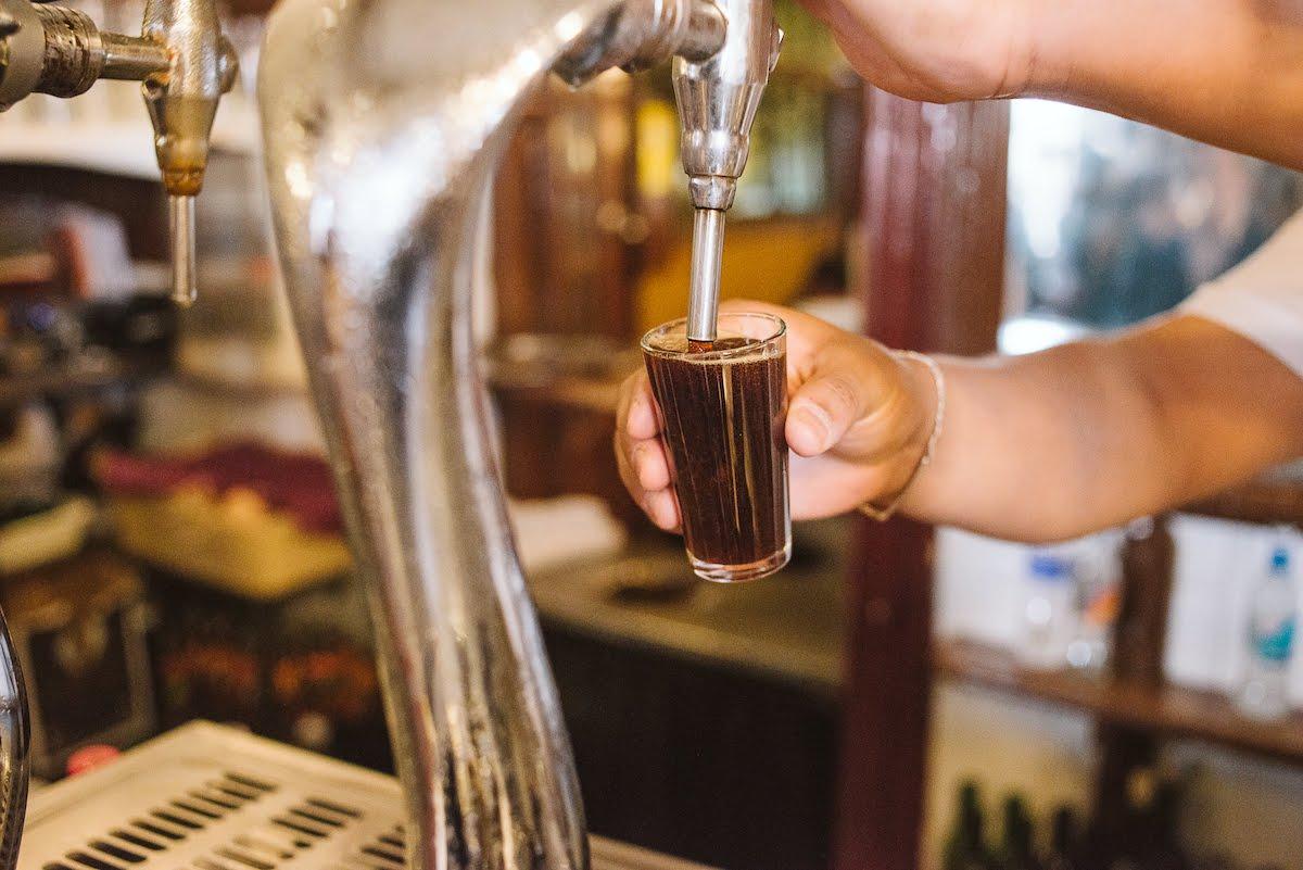 Cerca de un camarero vertiendo el vermú de un grifo en un vaso pequeño