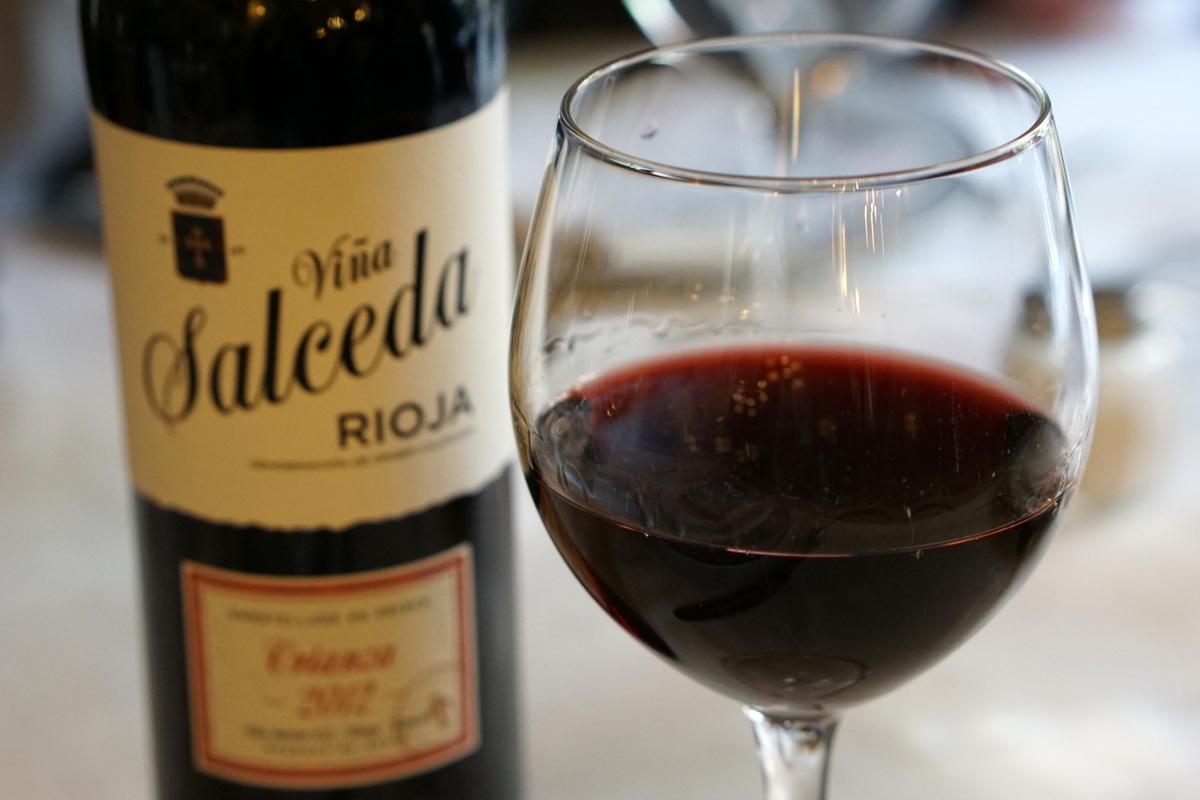 Cerca de una copa de vino tinto con la botella detrás de él