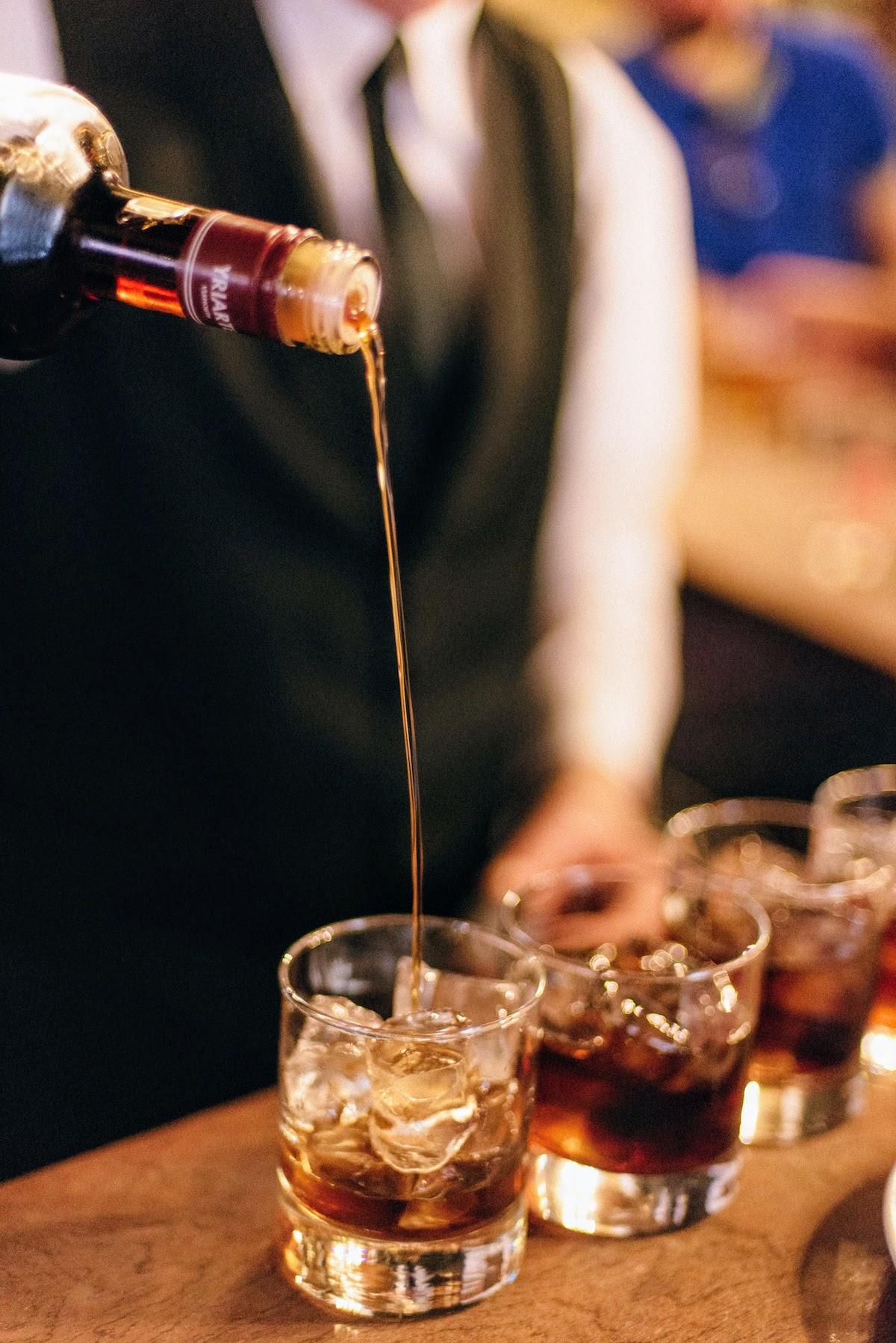 Camarero vertiendo vermú de una botella en tres vasos con hielo.