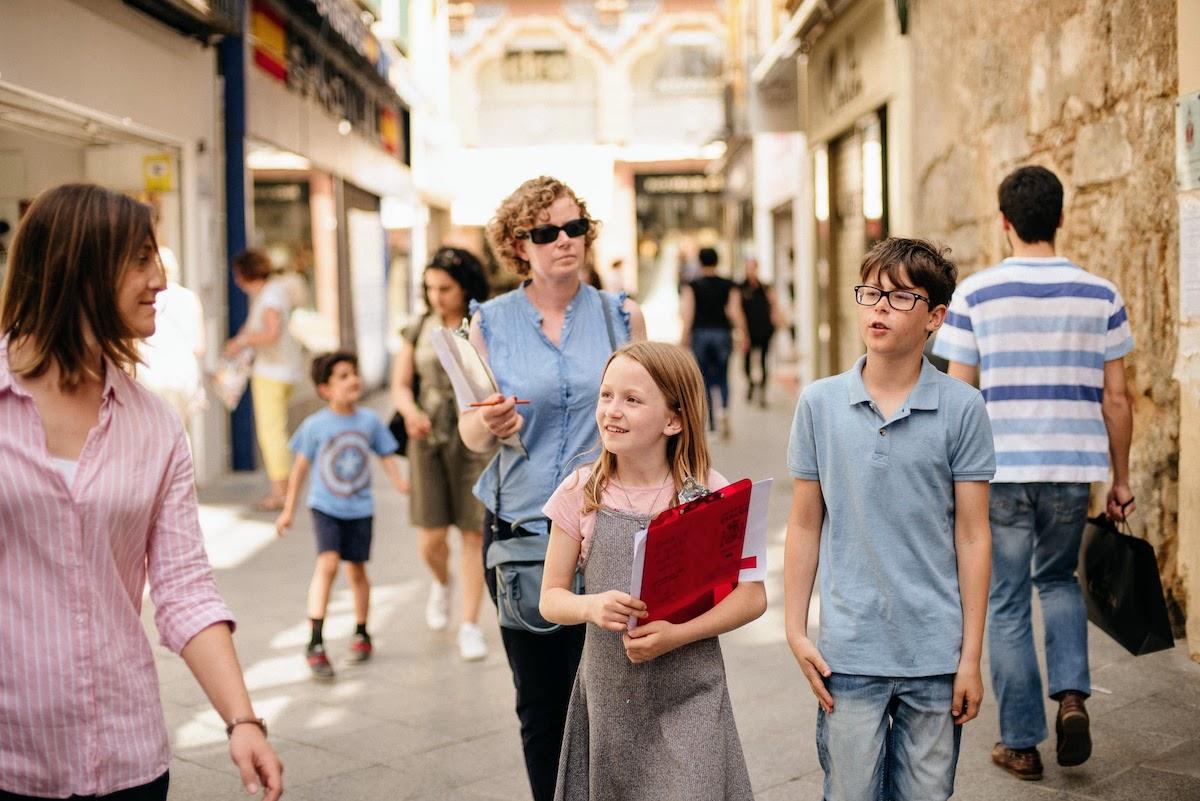 Una niña que lleva un portapapeles caminando por una ciudad ajetreada con un niño y dos mujeres