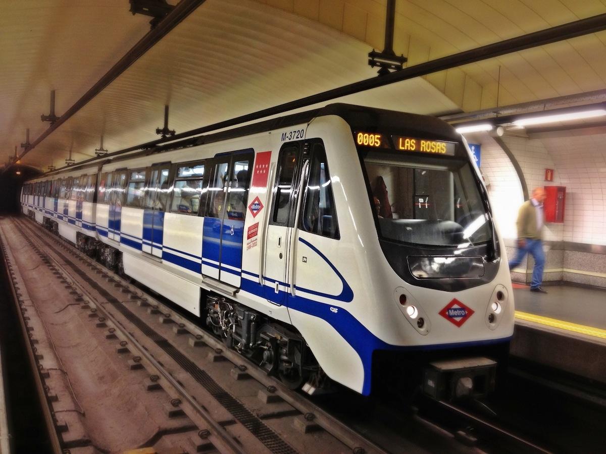 Un tren blanco y azul del metro de Madrid llegando a una estación.