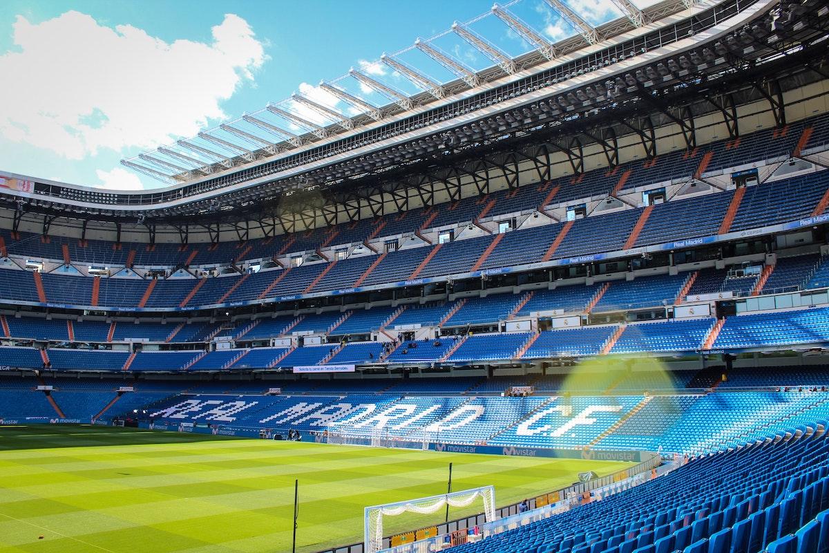 Vista interior de un gran estadio de fútbol vacío con césped verde y asientos azules, algunos pintados de blanco para deletrear el REAL MADRID CF.