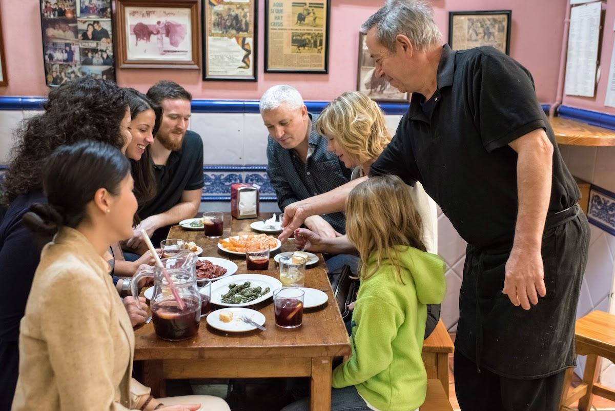 Una familia sentada alrededor de una pequeña mesa de madera llena de platos compartidos mientras un camarero pone más comida en la mesa.